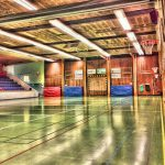 looking into a school gym with bleachers on the left wooden floors and large mats stored against far wall and basketball hoop on right wall