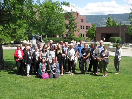 The 30 participants in the community partners' meeting pose for a group photo in the sun at UBC Okanagan campus.